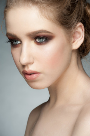 Studio portrait of beautiful young woman with stylish makeup smoky eyes photo