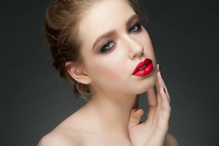 Studio portrait of beautiful young woman with stylish makeup with red lipstick  photo