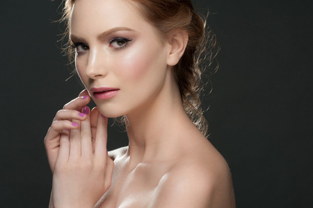 Studio portrait of beautiful young woman with stylish makeup and manicure photo