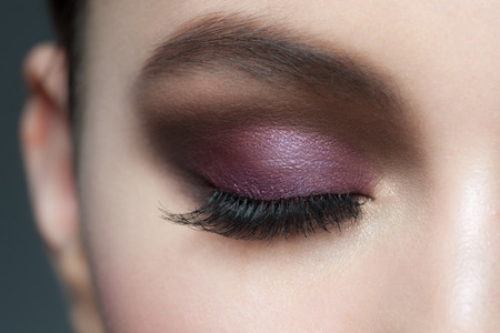 closed eye: Closeup of beautiful woman eye with bright violet stylish makeup with long lashes Stock Photo