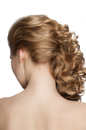 Woman with curly blond hair with beautiful hairstyle. Isolated on white background, rear view photo