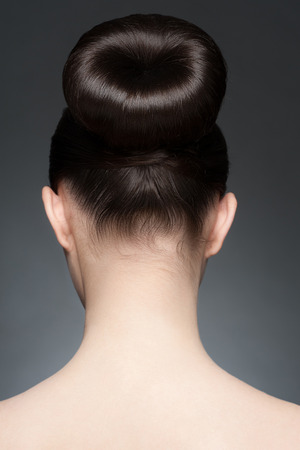 Portrait of young beautiful woman with elegant hairstyle, hair bun. Rear view 版權商用圖片