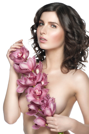 Sexy young woman holding a pink orchids branch. Isolated on white background, healthcare and beauty concept photo