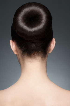Portrait of young beautiful woman with elegant hairstyle, hair bun. Rear view photo