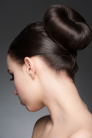 buns: Portrait of young beautiful woman with creative elegant hairstyle, hair bun. Rear view