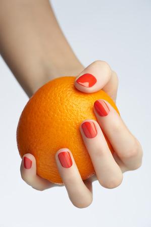 Closeup image of woman hand with beautiful orange manicure holding orange photo