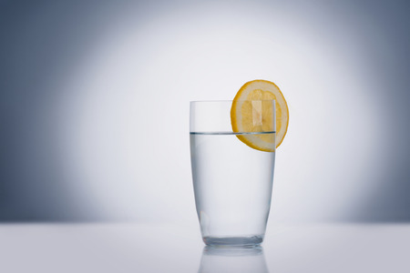 lemon water: Glass of water with lemon, isolated Stock Photo