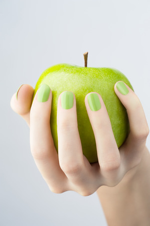 Closeup image of woman hand with beautiful green manicure holding green apple photo
