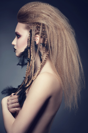 hair feathers: Studio portrait of attractive young woman with creative bright makeup and hairstyle with black feathers