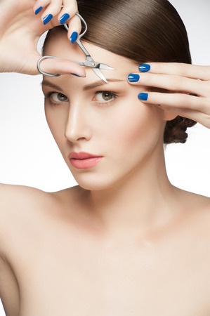 tweezing eyebrow: Young beautiful woman with fresh makeup cut her eyebrows, healthcare and beauty concept