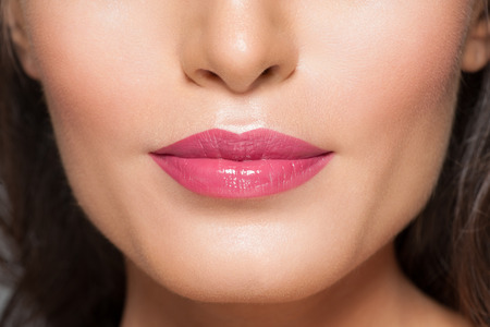 lapiz labial: Primer plano de hermosos labios con l�piz labial de color rosa sexy Foto de archivo