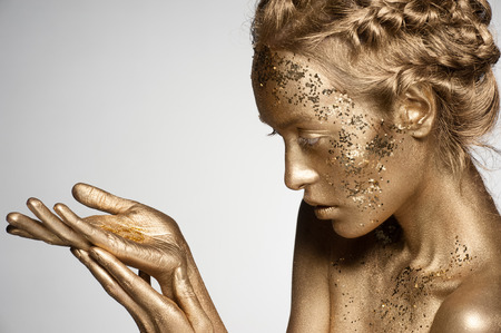 glitter makeup: Portrait of beautiful woman with golden makeup and bodyart holding golden sparkles on her palm