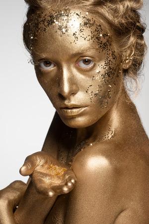 body paint: Retrato de mujer hermosa con maquillaje de oro y bodyart celebración chispas de oro en su palma Foto de archivo
