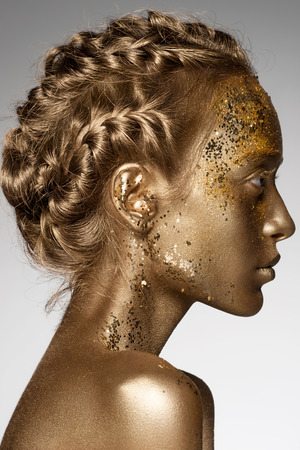 gold colour: Portrait of beautiful woman with golden makeup and bodyart