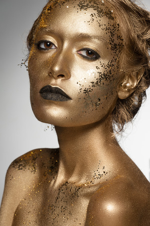 glitter makeup: Portrait of beautiful woman with golden makeup and bodyart