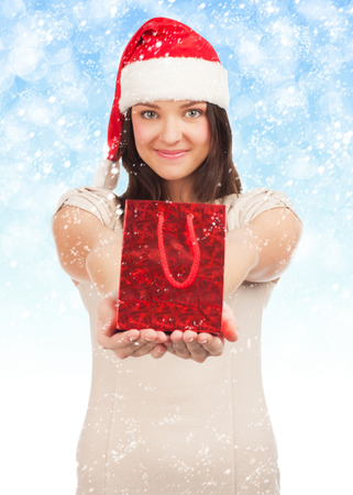 Excited woman in Santa hat with christmas gift box looking surprised photo