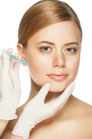 Cosmetic injection of botox to the pretty woman face. Isolated on white background photo