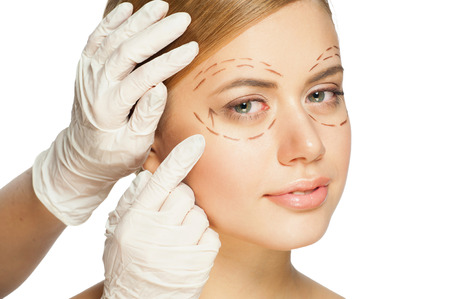 beautiful blonde woman: Beautiful young caucasian woman with perforation lines on her face before plastic surgery operation. Beautician touching woman face. Stock Photo
