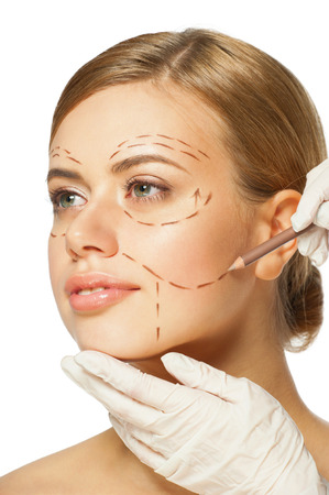 Beautiful young caucasian woman with perforation lines on her face before plastic surgery operation. Beautician touching woman face. photo