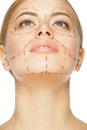 plastic surgery: Beautiful young caucasian woman with perforation lines on her face before plastic surgery operation. Beautician touching woman face. Stock Photo