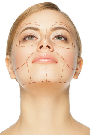 chin: Beautiful young caucasian woman with perforation lines on her face before plastic surgery operation. Beautician touching woman face. Stock Photo