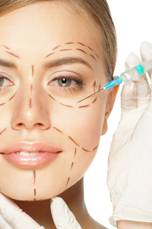 Beautiful young caucasian woman with perforation lines on her face before plastic surgery operation. Beautician touching woman face. Stock Photo