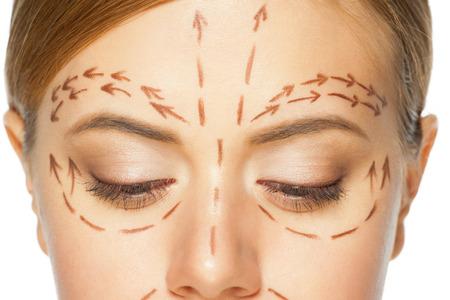 femme chatain: Belle jeune femme caucasien avec des lignes de perforation sur son visage avant op�ration de chirurgie plastique. Esth�ticienne visage de femme touchante.