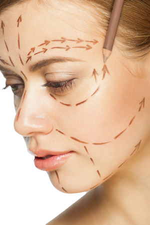 beautiful people: Beautiful young caucasian woman with perforation lines on her face before plastic surgery operation. Beautician touching woman face. Stock Photo