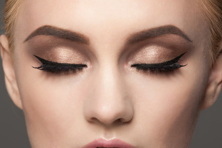 ojos marrones: Imagen del primer de la mujer cerró los ojos con maquillaje hermoso brillante. Maquillaje con lápiz de ojos y pestañas Falce Foto de archivo