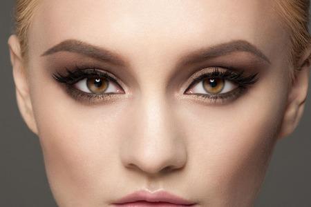 ojos marrones: Imagen del primer de la mujer hermosa ojos con maquillaje brillante de lujo. Maquillaje con lápiz de ojos y pestañas Falce