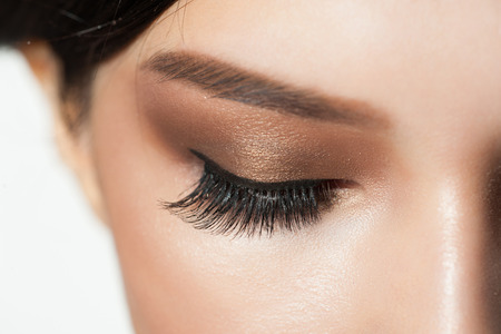 woman fashion: Closeup image of closed woman eyes with beautiful bright makeup. Makeup with eyeliner and falce eyelashes