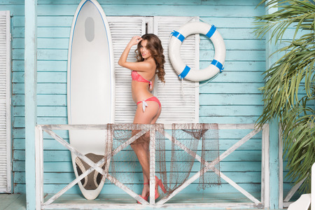Young beautiful caucasian woman with long curly hair and slim body wearing swimsuit with surfboard photo