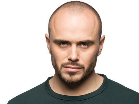 grumpy: Studio portrait of handsome young grumpy man looking in camera, isolated on white Stock Photo