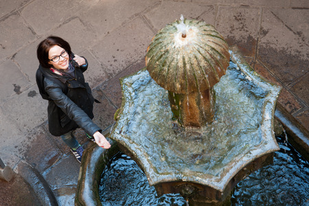Young woman backpacker tourist in Europe looking the fountain in Barcelona, Spain photo