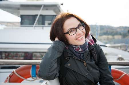 Young woman sitting on boat, looking at camera and smiling photo