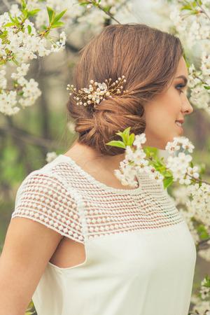 hairdo: Beautiful Girl in spring garden. Girl with bridal hairstyle. Stock Photo