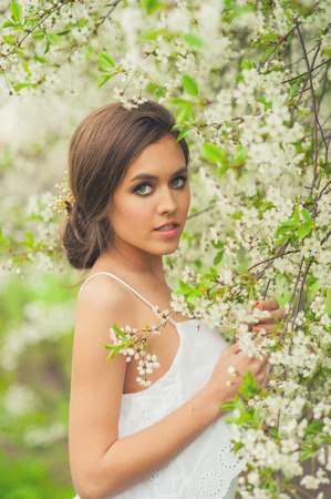 spring time: Beautiful Girl in spring garden. Girl with white flowers, spring time. Stock Photo