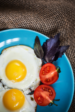 side plate: Fried eggs sunny side up served on blue plate with tomato and fresh herbs
