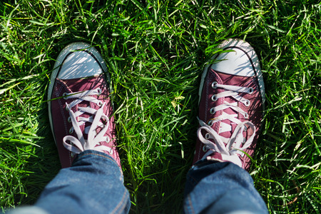 Image of male feet in boots on green grass outdoors