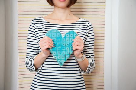 ceramic heart: Blue ceramic heart in woman hands Stock Photo