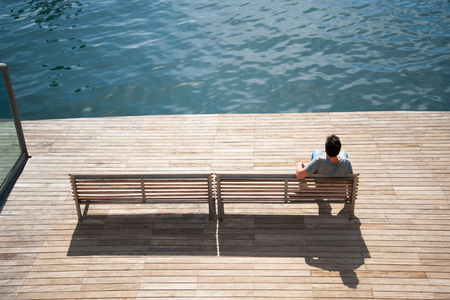 Handsome young man sitting alone and looking out to the sea photo