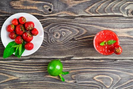 erdbeer smoothie: Strawberry smoothie with fresh berries on wooden background Lizenzfreie Bilder