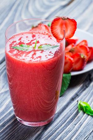erdbeer smoothie: Erdbeer-Smoothie mit frischen Beeren auf Holzuntergrund