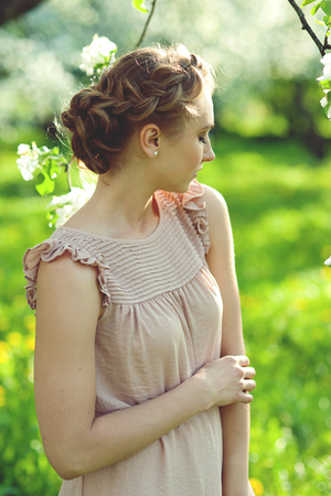 updo: Portrait of girl with beautiful updo hairstyle with tress in summer garden, summertime Stock Photo