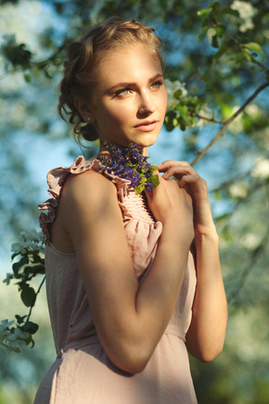 tress: Beautiful girl with makeup and hairdo with tress holding violet flowers in her hand, summertime. Stock Photo