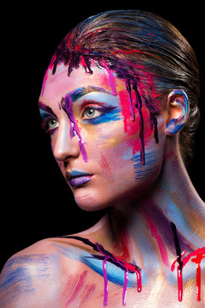 coloured: Portrait of pretty girl with creative art makeup painted different colors. Body art