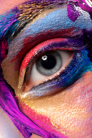 Closeup image of woman eye with creative makeup painted different colors. Looking at camera