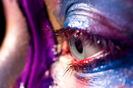 entice: Closeup image of woman eye with creative makeup painted different colors Stock Photo