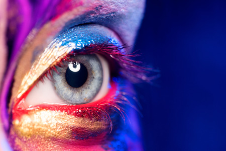 painted face: Closeup image of woman eye with creative makeup painted different colors Stock Photo