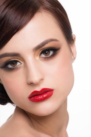 ojos marrones: Retrato de joven bella mujer con maquillaje de moda. Maquillaje con sombras doradas y los labios rojos Foto de archivo